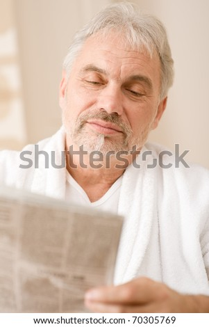 Senior mature man thoughtful read newspaper wear bathrobe