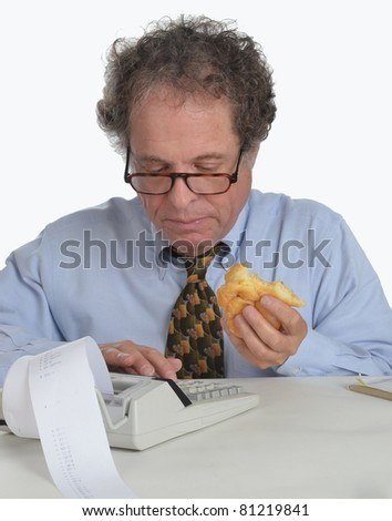 Senior mature man working on calculator/Senior Working on Financials/Man in blue shirt working on a calculator