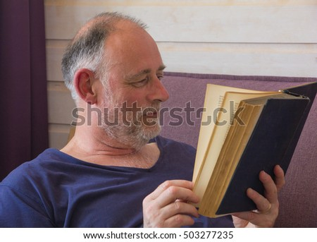 Senior men have free time and reading a old book  with  interest