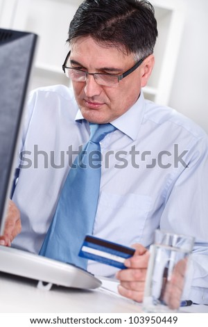 Senior men sitting front computer with credit card , ready for shopping on-line - stock photo