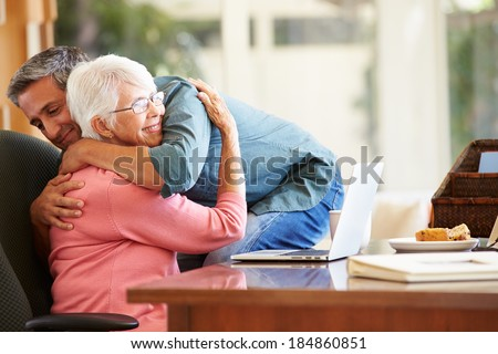 Senior Mother Being Comforted By Adult Son - stock photo