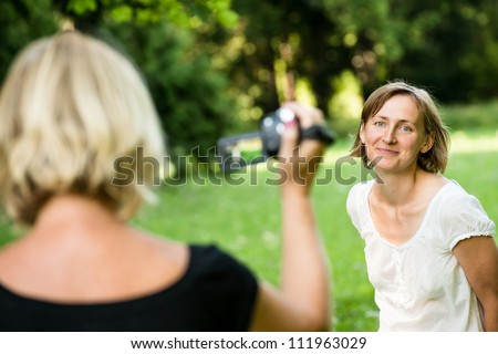 Senior mother is taking video of her adult daughter in nature with camcorder - stock photo