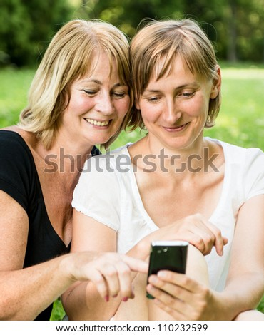 Senior mother showing on mobile phone to her adult child - outdoor in nature - stock photo