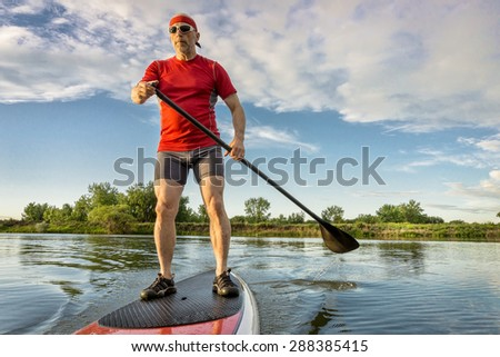 senior muscular male paddler enjoying paddling on stand up paddleboard, calm lake in summer scenery - stock photo