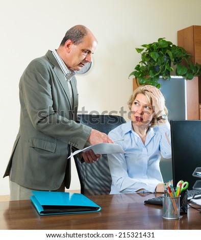 Senior office manager scolding aged secretary for mistake - stock photo