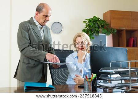 Senior office manager scolding elderly female secretary for mistake - stock photo