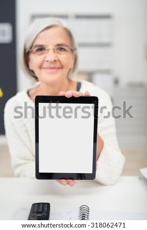 Senior Office Woman Showing a Tablet Screen with Copy Space While Sitting at her Desk. - stock photo