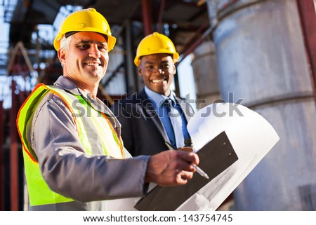senior oil industry worker holding clipboard and blueprint with manager in plant - stock photo