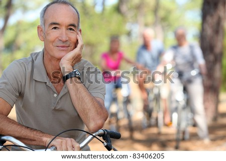 Senior on a bike with friends in the background - stock photo