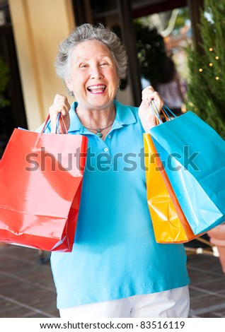 Senior on a shopping trip, excited about her bargains. - stock photo