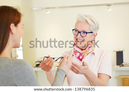 Senior optician giving new glasses to female customer - stock photo