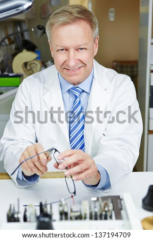 Senior optician repairing glasses with pliers in a workshop - stock photo