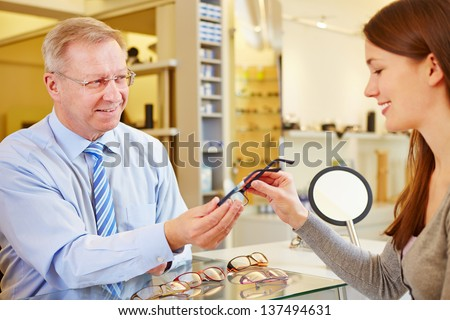 Senior optician selling new glasses to a young female customer - stock photo