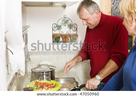 Senior or best ager couple cooking dinner together in their home kitchen, doing salad and preparing minced meat in a pan - stock photo