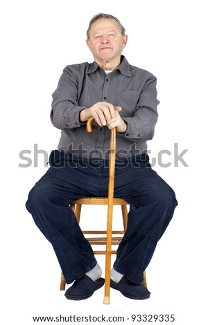 Senior or old man sitting down on old wooden chair with his cane to rest, wearing blue corduroy and slippers, isolated on white.
