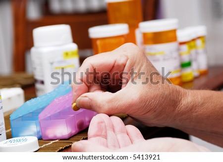 Senior organizing pill box - stock photo