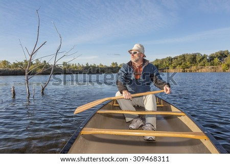 senior paddler enjoying morning sun on lake in a canoe, Riverbend Ponds Natural Area, Fort Collins, Colorado