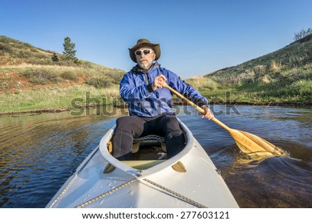 senior paddler in a decked expedition canoe on Horsetooth Reservoir, Fort Collins, Colorado, springtime scenery - stock photo