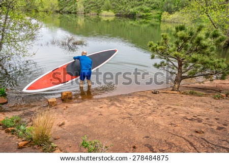 senior paddler launching  red SUP paddleboard on a rocky shore of a lake - Horsetooth Reservoir, Fort Collins, Colorado - stock photo