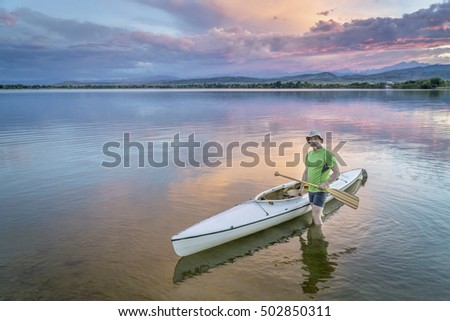 senior paddler with a decked expedition canoe on a calm lake with Rocky Mountains and Longs Peak in background