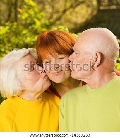 Senior parents kissing their daughter outdoors - stock photo