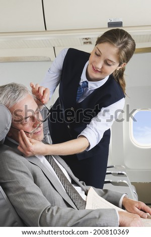 Senior passenger sleeping on airplane while air hostess is removing glasses - stock photo