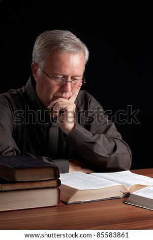 Senior pastor meditating and searching guidance - stock photo