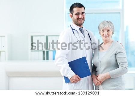Senior patient and successful doctor looking at camera in hospital - stock photo