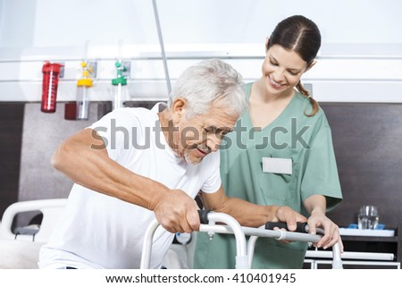 Senior Patient Being Assisted By Female Nurse In Using Walker - stock photo