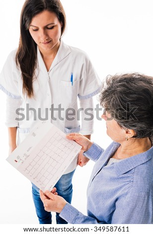 Senior patient is looking at electrocardiogram while standing close to young doctor - isolated on white