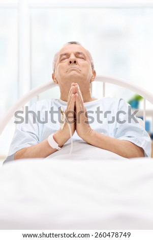 Senior patient lying in hospital bed and praying to god  - stock photo