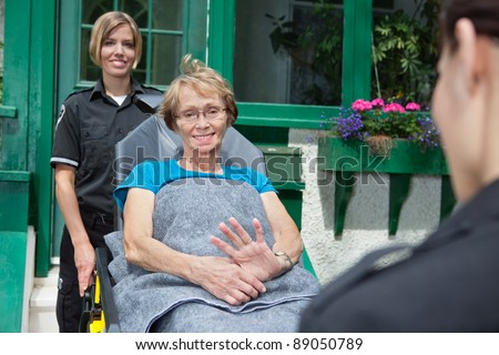 Senior patient on stretcher being pushed by emergency medical professionals. Shallow DOF, critical focus on patient - stock photo