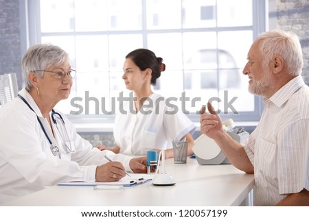 Senior patient sitting at doctor's room, consulting with female doctor. - stock photo