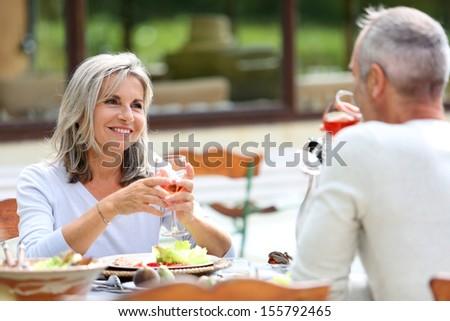 Senior people having lunch in garden - stock photo