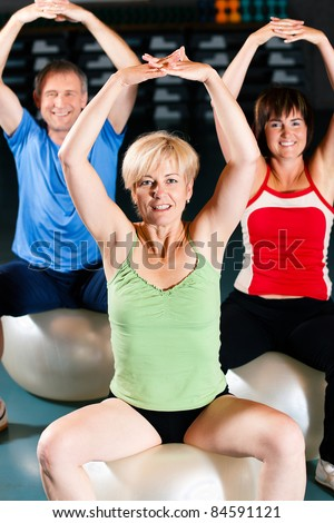 Senior people in a gym exercising with fitness ball