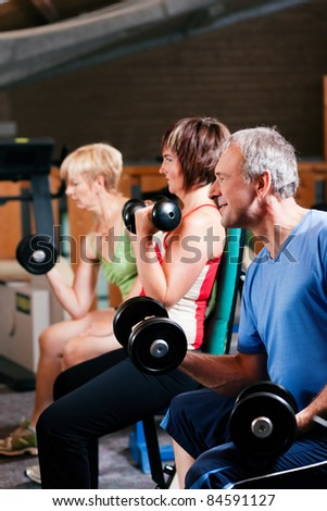 Senior people in a gym exercising with weights - stock photo