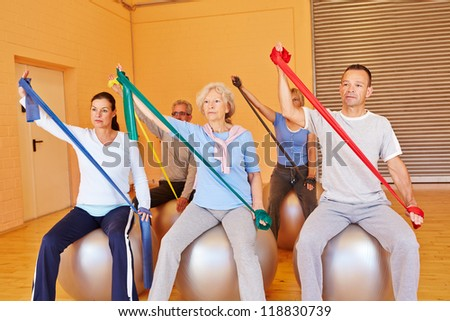Senior people in gym doing back training with exercise band - stock photo