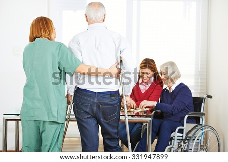 Senior people in nursing home with geriatric garegiver - stock photo