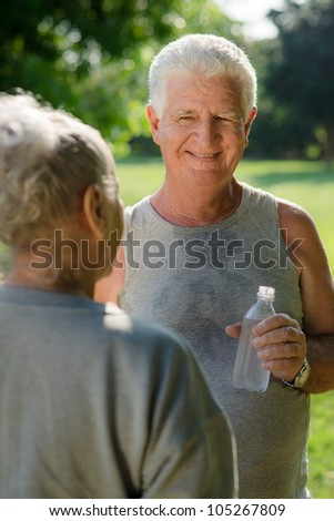Senior people, old man and woman talking and drinking water after exercising in park - stock photo