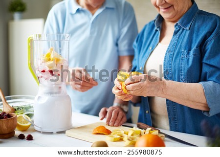 Senior people peeling fruits for smoothie