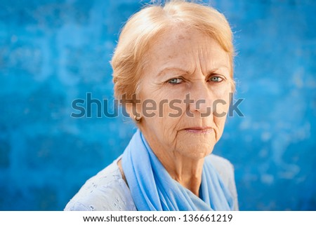 Senior people portrait, happy sad blonde woman in blu clothes looking at camera against blue wall - stock photo