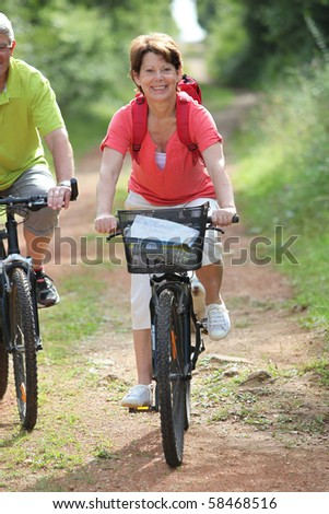 Senior people riding bicycle in the countryside - stock photo