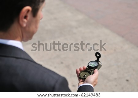 Senior people series - portrait of mature business man looking at compass with copy space - stock photo