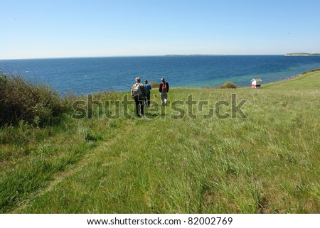 Senior people  with backpacks hiking walking by the sea ocean