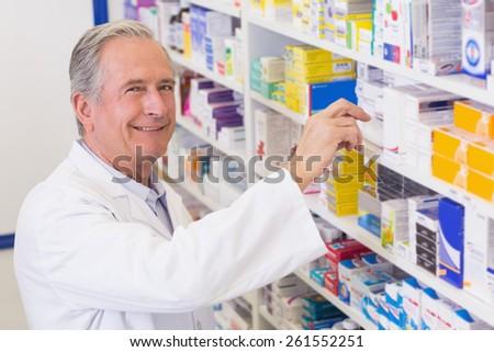 Senior pharmacist taking medicine from shelf at the hospital pharmacy - stock photo