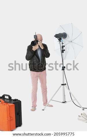 Senior photographer taking a photograph in studio - stock photo