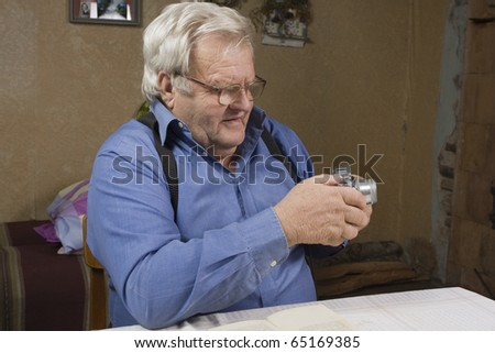 Senior photographer with his old camera. Staring at the camera in their hands. - stock photo