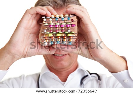 Senior physician holding different pills in front of his face - stock photo
