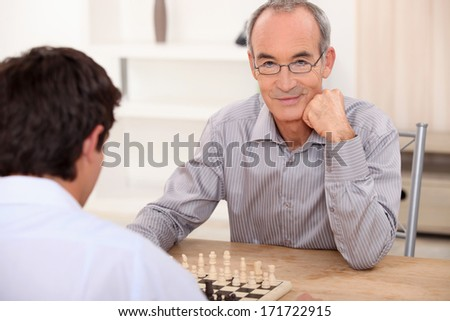 senior playing chess with grandson