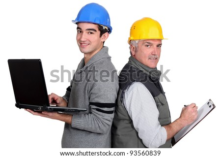 senior plumber and junior standing back to back with laptop and clipboard - stock photo